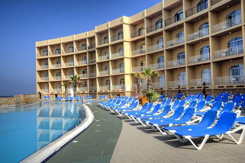 A tágas, kényelmes és rendkívül népszerű szálloda Málta északi részén, a Mellieha Bay öbölben található közvetlen a tengerparton, a repülőtértől kb. 22 km-re, Gozo és Comino szigetével szemben.